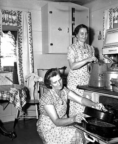 Women cooking at a stove.