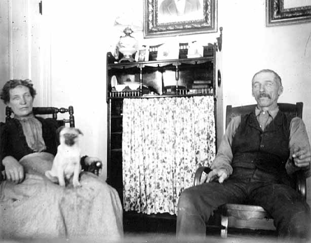 Man and woman seated in home interior, Morrison County