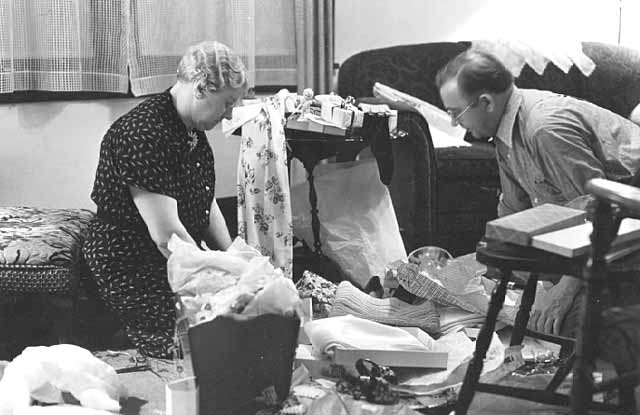 Man and woman opening Christmas presents.