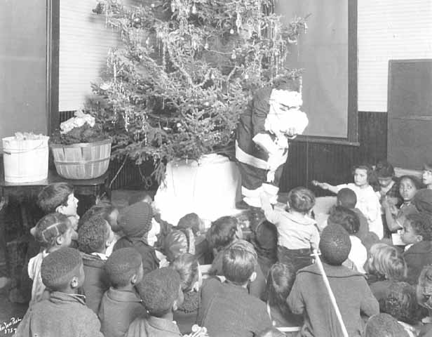 Santa passing out Christmas presents to children at Phyllis Wheatley House, Minneapolis.