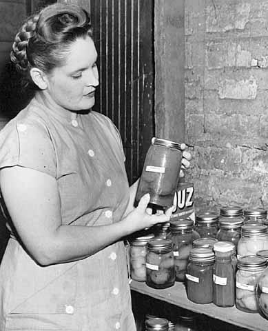 Woman with home canned food to supplement food purchased under rationing