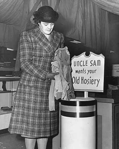 nn Ginn of the War Production Board Salvage Committee donating hosiery for defense.