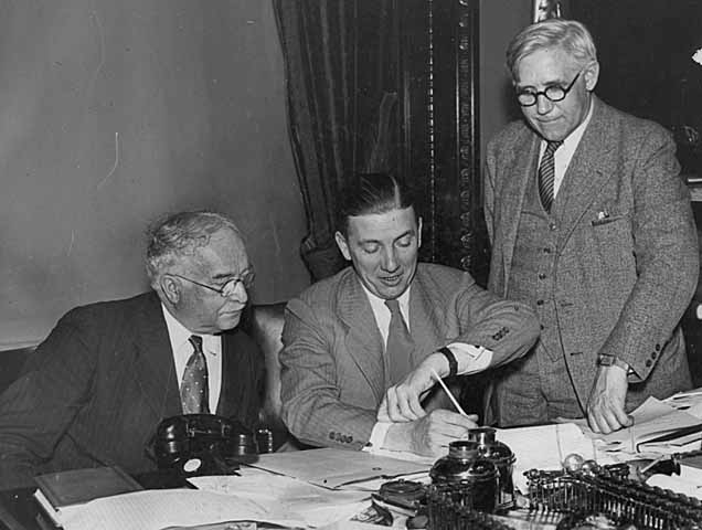 Governor Floyd B. Olson signing the Mortgage Relief Bill in the presence of Representative Leonard Ericksson and George C. Stiles, attorney for the Property Owners Association of Minnesota