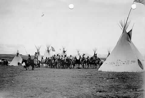 Unidentified members of the Blackfeet Tribe, on horseback, Intertribal Encampment, Browning, Montana.