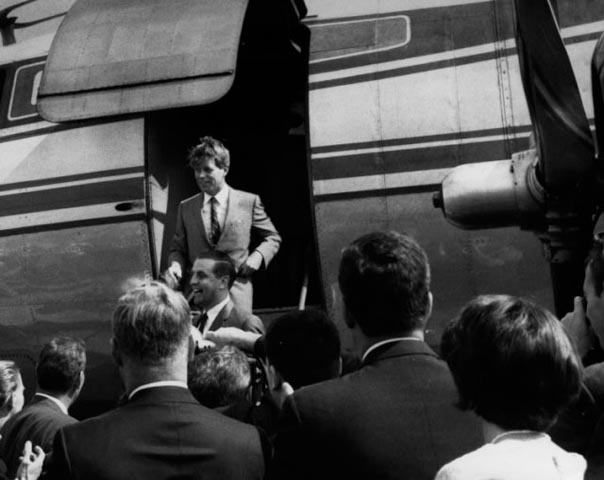 Senators Walter Mondale and Robert Kennedy exit a plane, 1966