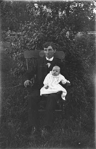 Man with baby on his knee, Morrison County.
