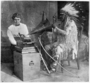 Frances Densmore with Mountain Chief (Sioux), Chief is interpreting a recording with sign language, 1914